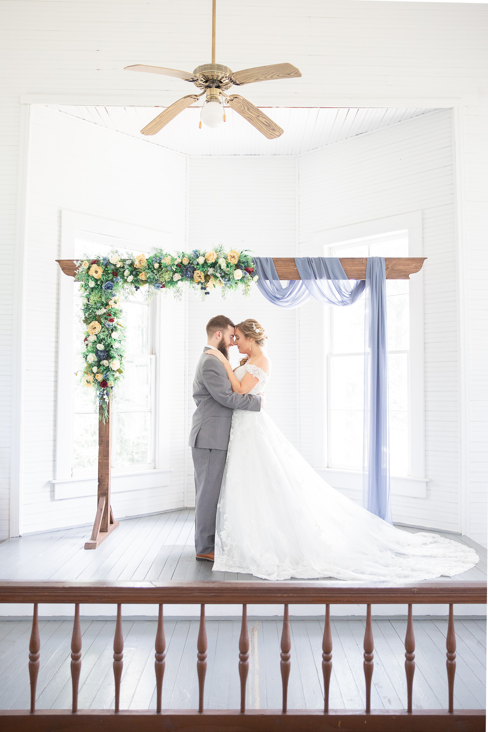 Annie Elise Photography | Ceremony | Bride and Groom portrait | Flower arbor | White Chapel | Slate Blue Wedding