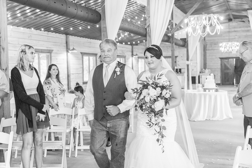 Annie Elise Photography | The Stables Venue | Vancleave, MS | Rustic Barn Wedding | bride walking down aisle | Black and White